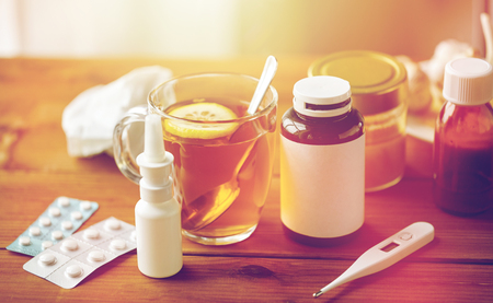 healthcare, traditional medicine and flu concept - cup of tea with lemon, thermometer and drugs on wooden table