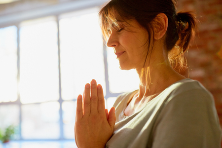 religion, faith, harmony and people concept - close up of yogi woman meditating at yoga studio