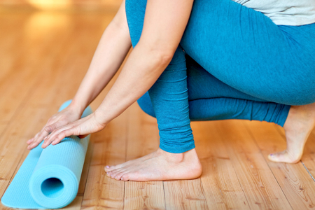 fitness, people and healthy lifestyle concept - close up of woman hands rolling yoga mat at gym or studio Lizenzfreie Bilder