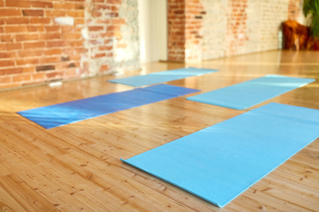 fitness, sport and healthy lifestyle concept - yoga mats on floor at gym or studio