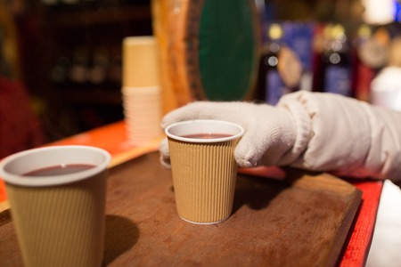 winter holidays, hot drinks and people concept - hand with cup of mulled wine at christmas market Lizenzfreie Bilder