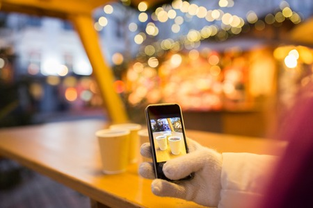 winter holidays, technology  and people concept - hand with mulled wine or hot chocolate drinks picture on smartphone at christmas market