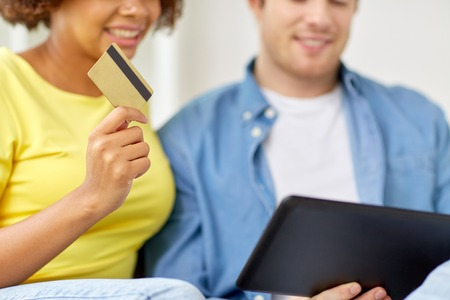technology, online shopping and people concept - happy couple couple with tablet pc computer and credit card