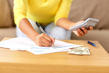 business, finances and people concept - woman with money, papers and calculator at home Stockfoto