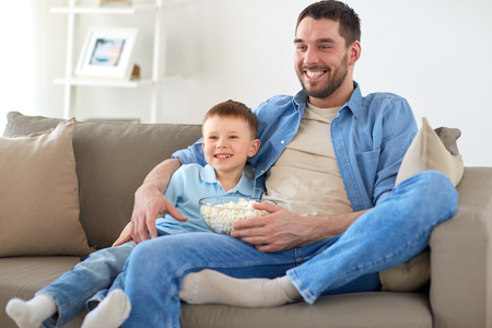 father and son with popcorn watching tv at home