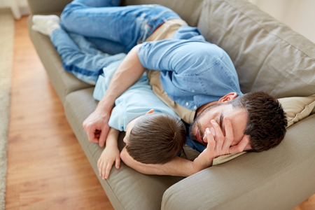 father and son sleeping on sofa at home Lizenzfreie Bilder