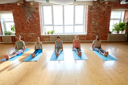 group of people doing yoga staff pose at studio