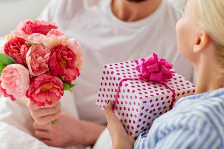 Cierre de pareja con regalo y flores en la cama Foto de archivo - 87213341