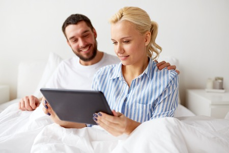 smiling happy couple with tablet pc in bed at home