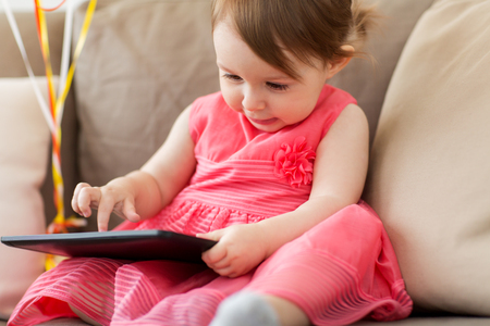 baby girl with tablet pc at home