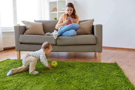 mother with smartphone and baby playing at home Lizenzfreie Bilder
