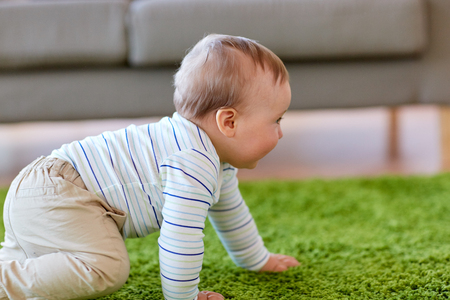 baby boy crawling on floor at home