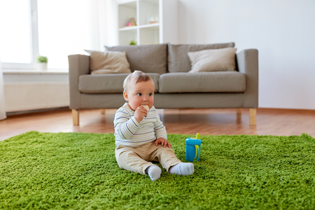 baby boy on floor and eating rice cracker at home Banco de Imagens