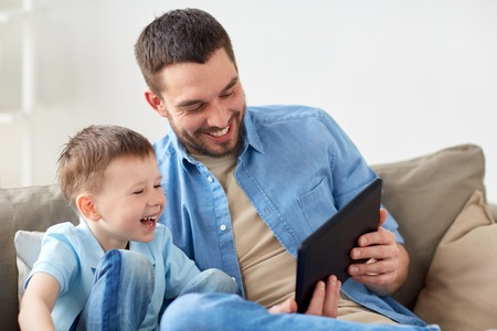 father and son with tablet pc playing at home Lizenzfreie Bilder