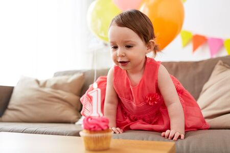 baby girl with birthday cupcake at home party