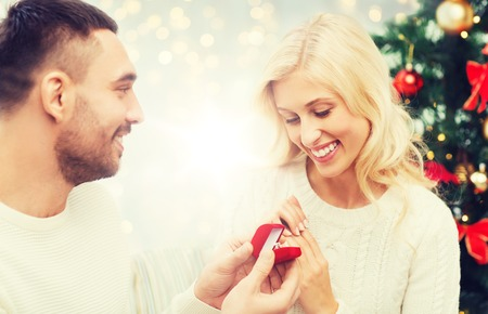 love, couple, proposal, holidays and people concept - happy man giving diamond engagement ring in little red box to woman over christmas tree and lights background Stock Photo