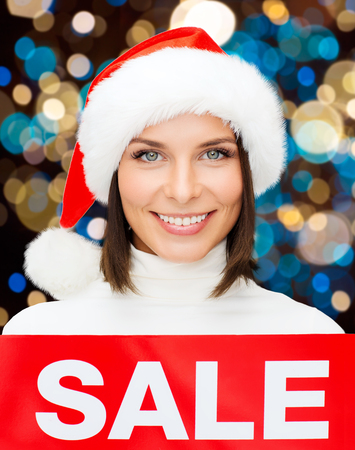 shopping, christmas and people concept - smiling woman in santa helper hat with red sale sign over lights background Stock Photo