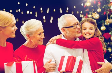 가족, 휴일 및 사람들이 개념 - 행복 한 조부모, 손녀와 어머니 선물 상자와 크리스마스 thee 통해 조명 배경