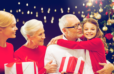 three generations: family, holidays and people concept - happy grandparents, granddaughter and mother with gift boxes and christmas thee over lights background Stock Photo