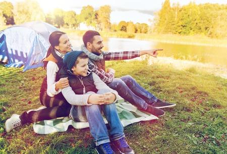 Concept de voyage, de tourisme et de randonnée - famille heureuse devant la tente au camping en montrant du doigt quelque chose Banque d'images - 87446001