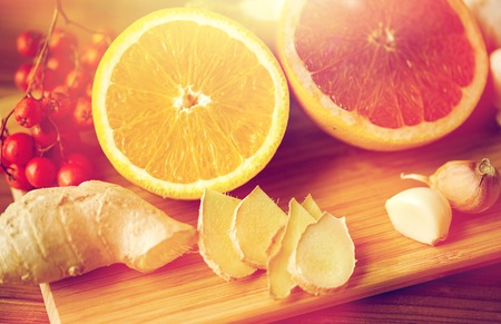 rowanberry: traditional medicine, cooking, food and ethnoscience concept - orange, grapefruit with ginger and garlic on wooden board