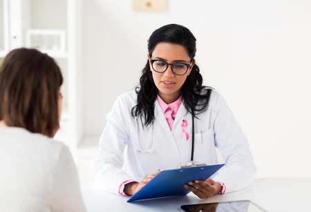 oncology and breast cancer concept - female doctor with pink awareness ribbon and patient at hospital
