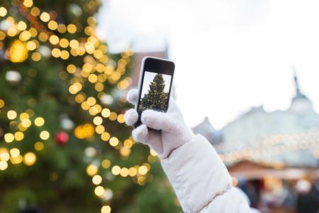 休日、技術と人のコンセプト - クリスマス ツリーを撮影スマート フォンと手