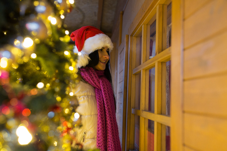 holidays and decoration concept - woman looking to santa house or shop window at christmas market