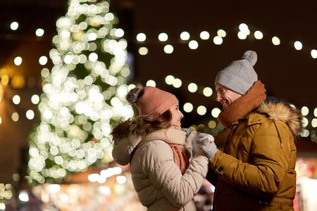 Vacaciones de invierno y concepto de la gente - feliz pareja joven sonríe en el árbol de navidad en la noche Foto de archivo - 87446080