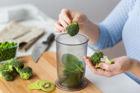 健康的な食事、離乳食、食事と料理の概念 - は、計量カップほうれん草にブロッコリーを追加する女性の手のクローズ アップ