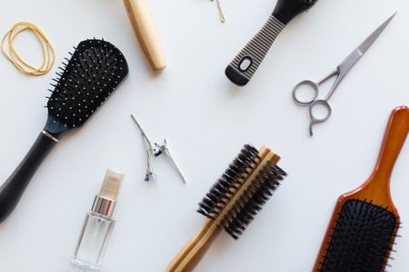 hair tools, beauty and hairdressing concept - scissors, different brushes, clips and styling spray on white background