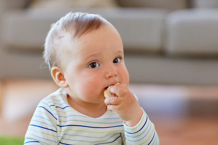 baby boy eating rice cracker at home