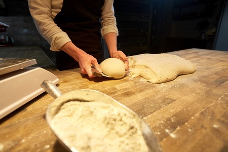 baker portioning dough with bench cutter at bakery Banco de Imagens