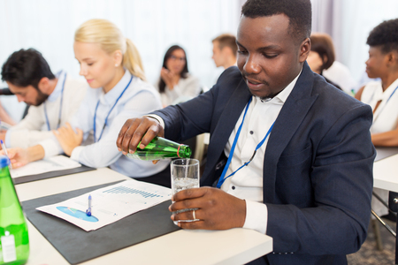 man drinking water: businessman drinking water at business conference Stock Photo