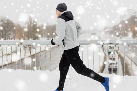 man running along snow covered winter bridge road Stock Photo