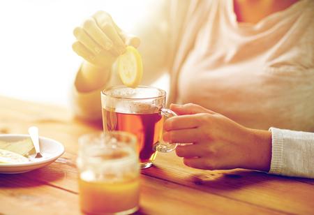 close up of ill woman drinking tea with lemon Stock Photo