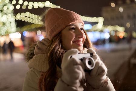 クリスマス マーケットでカメラを持つ幸せな若い女性