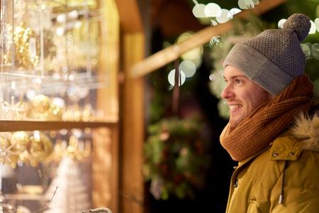 Gelukkige mens die het venster van de Kerstmismarkt bekijken Stockfoto - 87683624