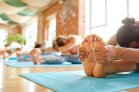 group of people doing yoga forward bend at studio Stock Photo