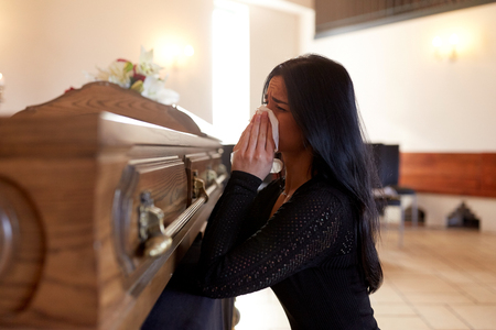 woman with coffin crying at funeral in church Imagens