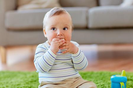 床で食べるおせんべい家に男の子の赤ちゃん 写真素材