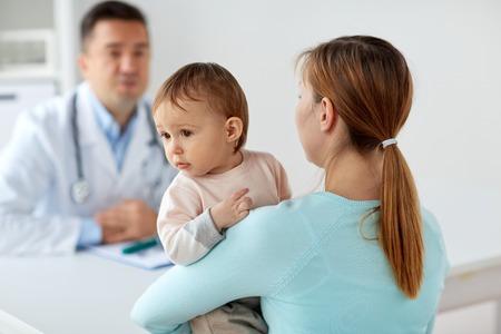 Mujer feliz con el bebé y doctor en la clínica Foto de archivo - 87689659