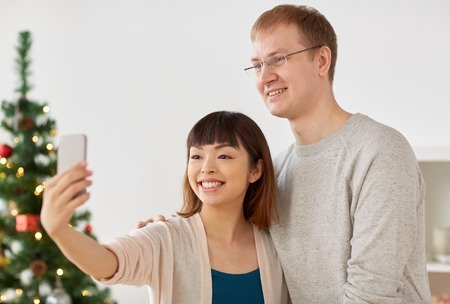 mixed-raced couple taking selfie at christmas