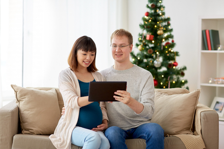 man and pregnant wife with tablet pc at christmas