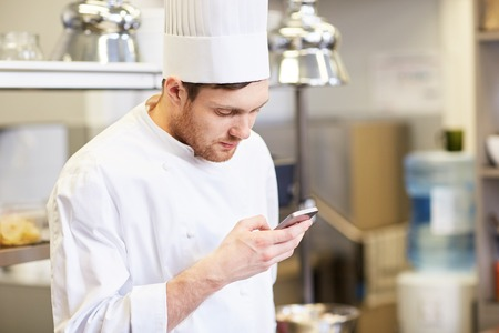 chef cook with smartphone at restaurant kitchen
