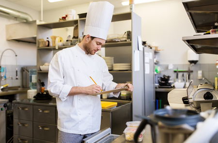 Chef con appunti che fanno la lavastoviglie in cucina Archivio Fotografico - 87957716