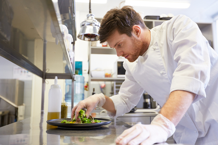 Feliz chef macho cocina comida en la cocina del restaurante