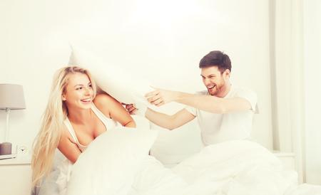 szczęśliwa para ma walkę na poduszki w łóżku w domu
