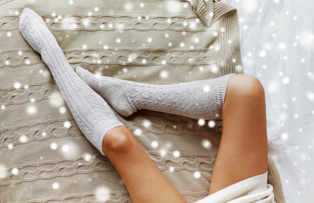 close up of woman legs in winter knee socks on bed Banco de Imagens