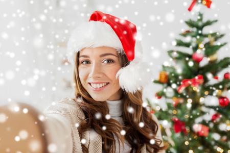 mujer en el sombrero de santa tomando autofoto en navidad